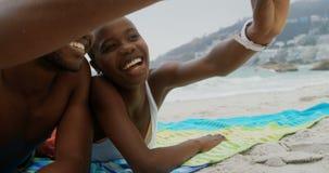 Ideia dianteira dos pares afro-americanos que tomam o selfie com telefone celular na praia 4k video estoque