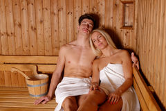 Pares novos que apreciam a sauna imagem de stock