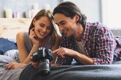 Ideia dianteira dos pares novos que guardam a câmera em uma cama Foto de Stock Royalty Free