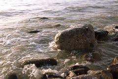Ideia do alvorecer no beira-mar com o céu claro ondas da ressaca e grandes pedras do pedregulho Fundo azul com espaço da cópia Fotografia de Stock