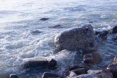 Ideia do alvorecer no beira-mar com o céu claro ondas da ressaca e grandes pedras do pedregulho Fundo azul com espaço da cópia Fotografia de Stock Royalty Free