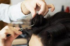 Ideia do close up da mão do barbeiro que penteia um penteado novo em uma cabeça do cliente no cabeleireiro imagens de stock