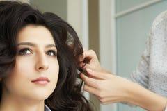 A ideia do close up da mão e o pente de um barbeiro que penteia um penteado novo em um cliente dirigem no cabeleireiro fotografia de stock royalty free