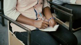 Ideia do close-up das mãos fêmeas africanas Mulher que senta-se em uma cadeira e que escreve no caderno Menina do estudante em um