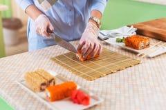 Ideia do close-up das mãos fêmeas nas luvas que cozinham os rolos de sushi japoneses tradicionais que cortam com a faca na cozinh Imagem de Stock