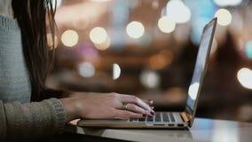Ideia do close-up das mãos fêmeas que datilografam no laptop Jovem mulher que senta-se perto da janela na noite e no uso Wi-Fi vídeos de arquivo