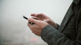 Ideia do close-up das mãos masculinas que guardam o telefone celular com écran sensível Homem novo que usa o smartphone no parque filme