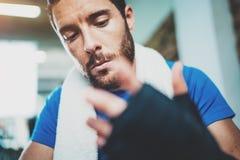 Ideia do close up das mãos prepairing do homem muscular do pugilista para a sessão de formação kickboxing dura no gym Amarração n foto de stock