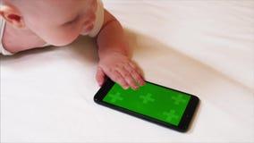 Ideia do close up de 6 meses adoráveis do bebê idoso que joga com smartphone filme