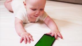 Ideia do close up de 6 meses adoráveis do bebê idoso que joga com smartphone video estoque