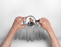 Ideia do close-up do man& x27; s entrega a lente de aumento de focalização no homem de negócios com sua mão levantada Foto de Stock Royalty Free
