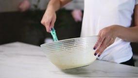 A ideia do close up do ` s da mulher entrega ingredientes de mistura para preparar a massa o na bacia usando o batedor de ovos Co video estoque