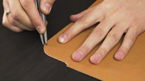 A ideia do close up do ` s do artesão entrega o trabalho com uma parte de couro na tabela video estoque