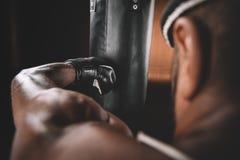 Ideia do close-up do treinamento tailandês do atleta de Muay no encaixotamento tailandês com saco de perfuração Foto de Stock