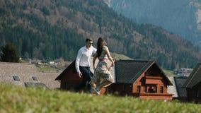A ideia do close-up dos pares felizes que correm nas montanhas no fundo das casas de madeira sutic filme