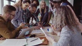Ideia do close-up do grupo de pessoas da raça misturada que está perto da tabela Equipe nova do negócio que trabalha no projeto j video estoque