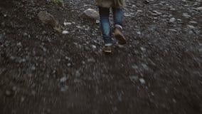 Ideia do close-up do pé masculino ansioso nas botas que correm longe de alguém com a maneira rochosa em Islândia vídeos de arquivo