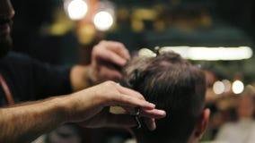 A ideia do close up do ` s do barbeiro entrega a execução de um corte de cabelo com as tesouras e o penteado do cliente Tiro Slow filme