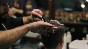 A ideia do close up do ` s do barbeiro entrega a execução de um corte de cabelo com as tesouras que guardam uma escova de cabelo  filme