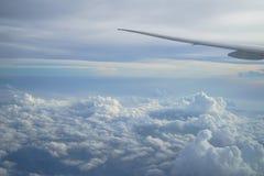 Ideia do cloudscape bonito com máscaras do fundo do céu azul da janela do plano do voo com asa do avião Imagens de Stock