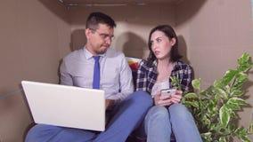 A ideia do conceito de pouca sala, casal novo huddled em uma caixa apertada video estoque