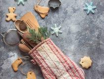 Ideia do papel de embrulho do Natal com luva do forno, utensílios da cozinha e cookies Imagens de Stock