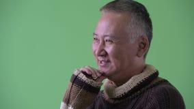 Ideia do perfil do pensamento japonês maduro feliz do homem pronto para o inverno filme