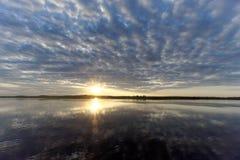 A ideia do por do sol dourado no rio com nuvens e no Sun refletiu nela, Volga, Rússia Fotos de Stock