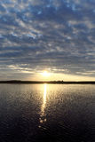 A ideia do por do sol dourado no rio com nuvens e no Sun refletiu nela, Volga, Rússia Fotografia de Stock