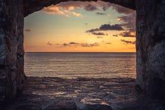 Ideia do por do sol bonito sobre o mar através da janela da construção velha com opinião dramática do céu e de perspectiva Imagem de Stock