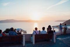 Ideia do por do sol cor-de-rosa-azul na ilha de Santorini ao mar, ao céu e às ilhas com os povos que sentam-se para trás no prime imagem de stock