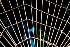 Ideia do reforço do metal sob a forma de uma Web contra a abertura, o sol no por do sol fotos de stock royalty free