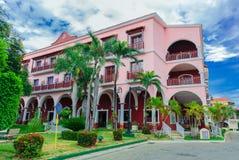 Ideia fabulosa de terras coloniais do hotel com construção principal à moda retro de convite bonita no jardim tropical no backgr  Fotografia de Stock