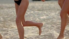 Ideia inferior do grupo de pés dos amigos que correm na água do mar em camisas do por do sol e do lance na praia Feliz alegre video estoque