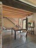 Ideia interior de uma sala de jantar que negligencia na entrada com assoalho concreto Fotografia de Stock