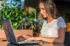 Ideia lateral da escrita nova do escritor fêmea em seu portátil ao sentar-se no café do parque Netbook de datilografia da menina  Imagem de Stock
