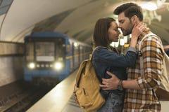 ideia lateral de pares à moda de viajantes que abraçam-se no metro fotografia de stock royalty free
