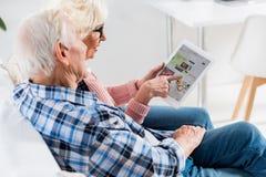 ideia lateral de pares superiores usando a tabuleta digital com ebay fotografia de stock
