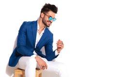 Ideia lateral de rir o homem novo elegante que senta-se na cadeira fotografia de stock royalty free