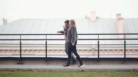 Ideia lateral de um par feliz que tem uma caminhada em um telhado de uma casa em uma cidade Homem moreno e mulher no amor vídeos de arquivo