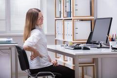Ideia lateral de uma dor de Suffering From Back da mulher de negócios fotografia de stock