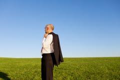 Ideia lateral do campo maduro de Standing On Grassy do homem de negócios Fotografia de Stock Royalty Free