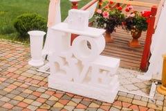 A ideia lateral do close-up dos sinais brancos ama colocado perto das flores Imagens de Stock Royalty Free