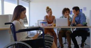 Ideia lateral do funcionamento deficiente caucasiano novo da fêmea na tabuleta digital contra três executivos filme