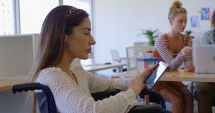Ideia lateral do funcionamento deficiente caucasiano novo da fêmea na tabuleta digital no escritório moderno 4k vídeos de arquivo