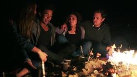 Ideia lateral do grupo de pessoas diverso que senta-se junto pelo fogo tarde na noite e que abraça-se, cozinhando vídeos de arquivo