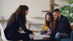 A ideia lateral do mediador imobiliário dos jovens e os compradores que olham a casa planeiam o assento na tabela na casa moderna video estoque