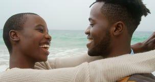 Ideia lateral dos pares afro-americanos que dançam junto na praia 4k video estoque