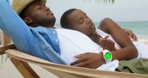 Ideia lateral dos pares afro-americanos que dormem em uma rede na praia 4k filme