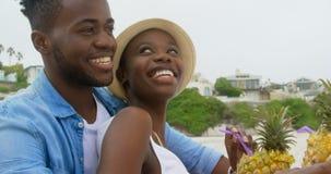 Ideia lateral dos pares afro-americanos que interagem um com o otro na praia 4k video estoque